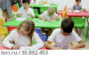 Купить «Group of diligent schoolkids drawing with cheerful female teacher at classroom», видеоролик № 30892453, снято 18 декабря 2018 г. (c) Яков Филимонов / Фотобанк Лори
