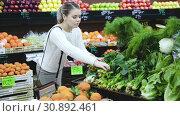 Купить «Portrait of young smiling woman doing shopping at vegetables store», видеоролик № 30892461, снято 12 февраля 2019 г. (c) Яков Филимонов / Фотобанк Лори
