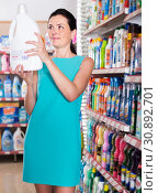 Купить «Attractive female want to buying softener in bottle», фото № 30892701, снято 6 июня 2017 г. (c) Яков Филимонов / Фотобанк Лори