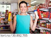 Купить «Woman choosing different sauces», фото № 30892705, снято 6 июня 2017 г. (c) Яков Филимонов / Фотобанк Лори