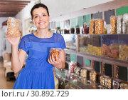 Купить «female customer choosing natural dried berries sold by weight in eco market», фото № 30892729, снято 13 июня 2017 г. (c) Яков Филимонов / Фотобанк Лори