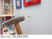 Купить «Молоток забивает гвоздь в стену, вешая рамки с фотографиями», фото № 30894509, снято 27 января 2019 г. (c) Иванов Алексей / Фотобанк Лори