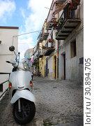 Купить «White scooter parked on a city street», фото № 30894705, снято 14 апреля 2019 г. (c) Алексей Кузнецов / Фотобанк Лори