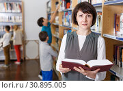 Female teacher browsing textbooks in library. Стоковое фото, фотограф Яков Филимонов / Фотобанк Лори