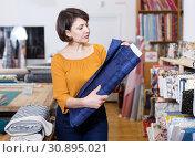 Купить «Woman looking for cloth in shop», фото № 30895021, снято 7 февраля 2019 г. (c) Яков Филимонов / Фотобанк Лори