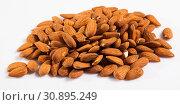 Купить «Close up of roasted almonds on white surface, no people», фото № 30895249, снято 17 июля 2019 г. (c) Яков Филимонов / Фотобанк Лори