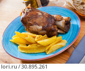 Купить «Close up of delicious baked pork knuckle with potatoes, served», фото № 30895261, снято 22 июля 2019 г. (c) Яков Филимонов / Фотобанк Лори