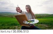 Купить «A young talanted woman sits on the meadow and draw - Measures image proportions», видеоролик № 30896513, снято 9 апреля 2020 г. (c) Константин Шишкин / Фотобанк Лори