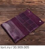 Купить «Handmade purple travel wallet lies on textured wooden backgroud closeup. Wallet is open and empty. Side view. Stock photo of businessman accessories.», фото № 30909005, снято 15 марта 2018 г. (c) easy Fotostock / Фотобанк Лори