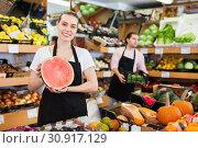 Купить «Young woman seller holding half of watermelon in hands in fruit store», фото № 30917129, снято 27 апреля 2019 г. (c) Яков Филимонов / Фотобанк Лори