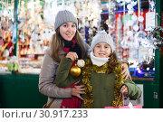 Купить «Smiling girl with woman are showing toys for X-mas tree», фото № 30917233, снято 19 декабря 2017 г. (c) Яков Филимонов / Фотобанк Лори