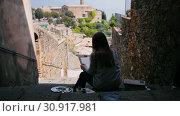 Купить «A young woman sits on the stairs and paints the buildings. Back view», видеоролик № 30917981, снято 26 января 2020 г. (c) Константин Шишкин / Фотобанк Лори