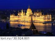 Купить «Beautiful night view of the Hungarian Parliament building and the Danube river with lights in the water in Budapest, Hungary», фото № 30924801, снято 1 июня 2019 г. (c) Яна Королёва / Фотобанк Лори