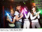 Купить «Young people in colorful beams on lasertag arena», фото № 30924997, снято 25 апреля 2018 г. (c) Яков Филимонов / Фотобанк Лори