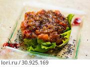 Купить «Image of salmon tartar with avocado and salad on glass plate», фото № 30925169, снято 24 июня 2018 г. (c) Яков Филимонов / Фотобанк Лори