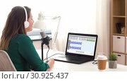Купить «woman with microphone recording podcast at studio», видеоролик № 30925437, снято 19 февраля 2020 г. (c) Syda Productions / Фотобанк Лори