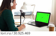 Купить «woman with microphone recording podcast at studio», видеоролик № 30925469, снято 19 февраля 2020 г. (c) Syda Productions / Фотобанк Лори