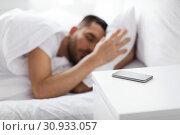 Купить «smartphone on bedside table near sleeping man», фото № 30933057, снято 6 мая 2017 г. (c) Syda Productions / Фотобанк Лори
