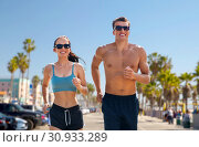 Купить «couple in sports clothes running along on beach», фото № 30933289, снято 1 августа 2018 г. (c) Syda Productions / Фотобанк Лори