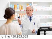 Купить «apothecary with cure and customer at pharmacy», фото № 30933365, снято 27 июня 2015 г. (c) Syda Productions / Фотобанк Лори