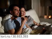 Купить «couple with popcorn watching tv at night at home», фото № 30933393, снято 27 января 2018 г. (c) Syda Productions / Фотобанк Лори