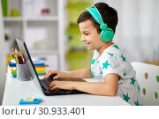 Купить «boy in headphones playing video game on laptop», фото № 30933401, снято 19 апреля 2018 г. (c) Syda Productions / Фотобанк Лори