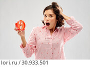 shocked young woman in pajama with alarm clock. Стоковое фото, фотограф Syda Productions / Фотобанк Лори