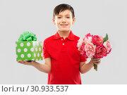 Купить «smiling boy with birthday gift box and flowers», фото № 30933537, снято 9 марта 2019 г. (c) Syda Productions / Фотобанк Лори