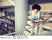 Купить «african student girl reading book at library», фото № 30933573, снято 19 июня 2016 г. (c) Syda Productions / Фотобанк Лори