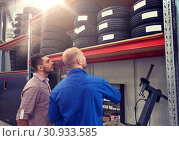Купить «mechanic and man choosing tires at car shop», фото № 30933585, снято 1 июля 2016 г. (c) Syda Productions / Фотобанк Лори