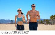 Купить «couple in sports clothes running along on beach», фото № 30933621, снято 1 августа 2018 г. (c) Syda Productions / Фотобанк Лори