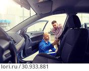 Купить «mechanic and man checking seat belt at car shop», фото № 30933881, снято 1 июля 2016 г. (c) Syda Productions / Фотобанк Лори