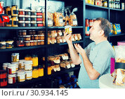 Купить «man looking at assortment of grocery products in shelves», фото № 30934145, снято 5 октября 2016 г. (c) Яков Филимонов / Фотобанк Лори