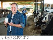 Купить «Smiling male farmer with milk on cow farm», фото № 30934213, снято 24 октября 2017 г. (c) Яков Филимонов / Фотобанк Лори