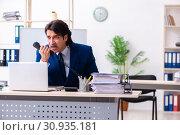 Купить «Young businessman sitting and working in the office», фото № 30935181, снято 18 марта 2019 г. (c) Elnur / Фотобанк Лори