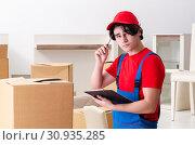 Купить «Young male contractor with boxes working indoors», фото № 30935285, снято 1 февраля 2019 г. (c) Elnur / Фотобанк Лори