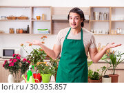 Купить «Young handsome man cultivating flowers at home», фото № 30935857, снято 25 февраля 2019 г. (c) Elnur / Фотобанк Лори