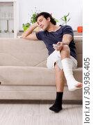 Купить «Leg injured young man suffering at home», фото № 30936405, снято 15 января 2019 г. (c) Elnur / Фотобанк Лори