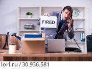 Купить «Young male employee being fired from his work», фото № 30936581, снято 17 апреля 2019 г. (c) Elnur / Фотобанк Лори