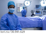 Купить «Female surgeon sitting with surgical mask in operation theater», фото № 30941629, снято 9 марта 2019 г. (c) Wavebreak Media / Фотобанк Лори