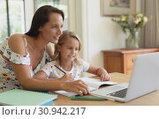 Купить «Mother helping her daughter with homework in a comfortable home», фото № 30942217, снято 12 марта 2019 г. (c) Wavebreak Media / Фотобанк Лори