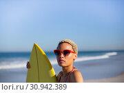 Купить «Woman standing with surfboard at beach in the sunshine», фото № 30942389, снято 15 марта 2019 г. (c) Wavebreak Media / Фотобанк Лори