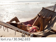 Купить «Woman using mobile phone while relaxing in a hammock on the beach», фото № 30942693, снято 15 марта 2019 г. (c) Wavebreak Media / Фотобанк Лори