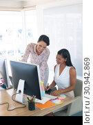 Купить «Female graphic designers discussing on computer at desk in a modern office», фото № 30942869, снято 19 ноября 2019 г. (c) Wavebreak Media / Фотобанк Лори