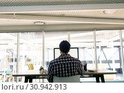 Купить «Male graphic designer working on computer at desk in a modern office», фото № 30942913, снято 16 марта 2019 г. (c) Wavebreak Media / Фотобанк Лори