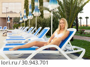 Купить «Young beautiful girl in a bathing suit resting on a lounger on a tropical resort with palm trees», фото № 30943701, снято 18 июля 2017 г. (c) katalinks / Фотобанк Лори