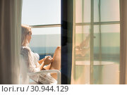 Купить «View through the window glass to the balcony. Beautiful girl drinks morning coffee and looks at summer sea.», фото № 30944129, снято 18 июля 2017 г. (c) katalinks / Фотобанк Лори