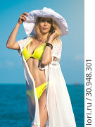 Купить «Gorgeous girl model on the beach on seaside in yellow swimsuit, white dress and big round hat», фото № 30948301, снято 11 июня 2017 г. (c) katalinks / Фотобанк Лори