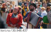 Купить «Tatarstan, Laishevo 25-05-2019: The man and the woman in national Russian clothes sing and play an accordion», видеоролик № 30948437, снято 16 июля 2019 г. (c) Константин Шишкин / Фотобанк Лори