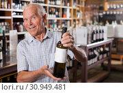 Купить «Man searchng wine in winehouse», фото № 30949481, снято 8 мая 2019 г. (c) Яков Филимонов / Фотобанк Лори